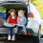 Zwei Kinder in einem Kofferraum sitzend